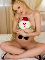 Sensual teen Tavia playfully stripping off her clothes in bed to show off her big breasts live