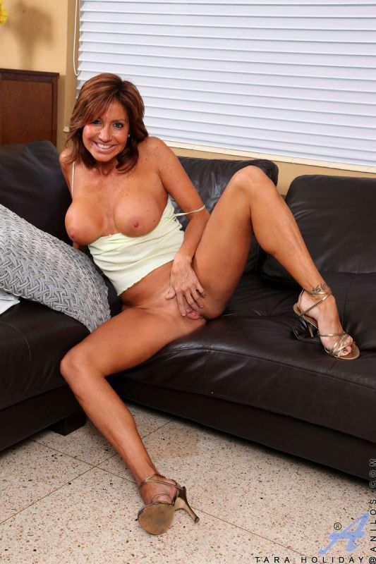 Brunette cougar proudly displays her big tits as she plays with ...