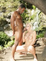 Busty Nicki Hunter goes right to work mouthing a black cock in her outdoor interracial scene